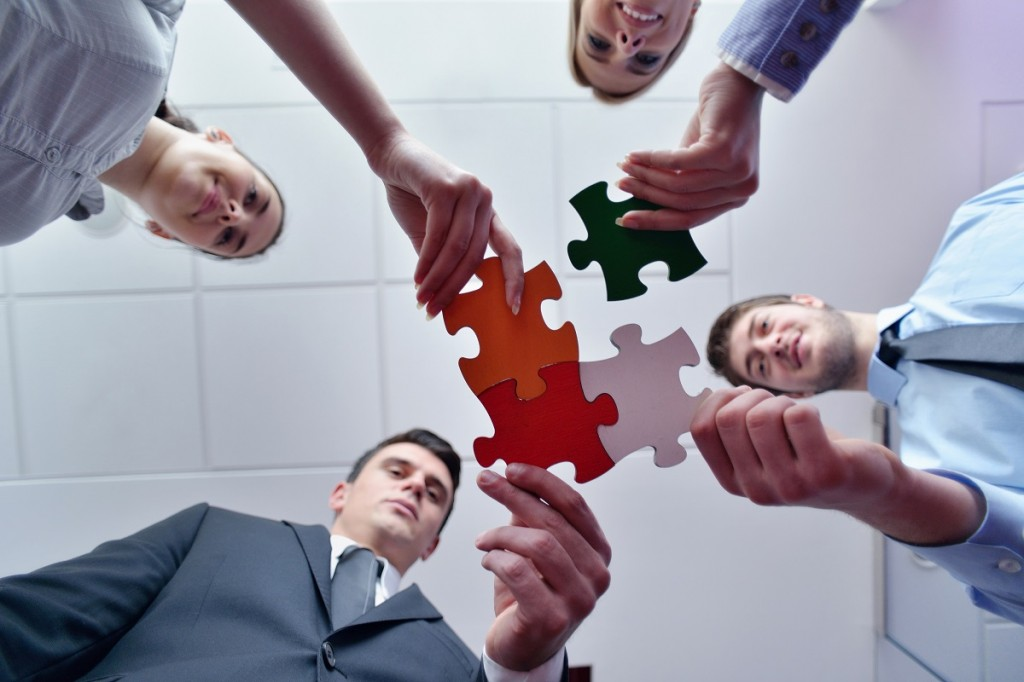 Group of business people assembling jigsaw puzzle and represent